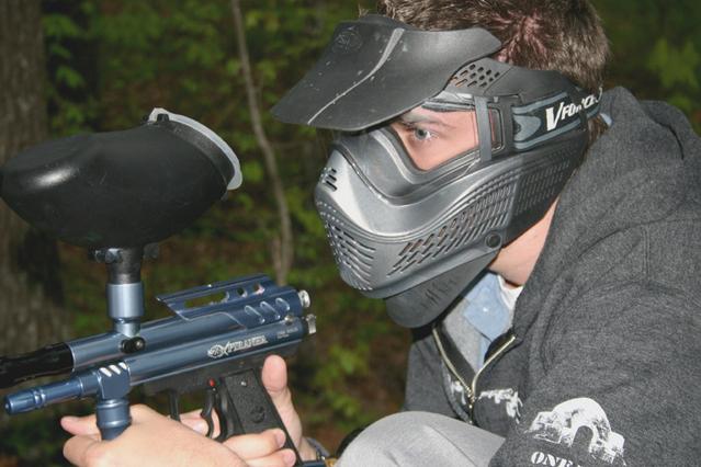 muž oděný v paintballové masce s puškou