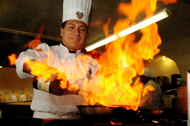 kuchař flambující pokrm ve své kuchyni