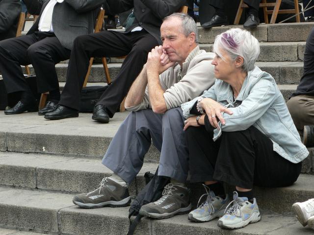 postarší pár sedící na schodech před památkou