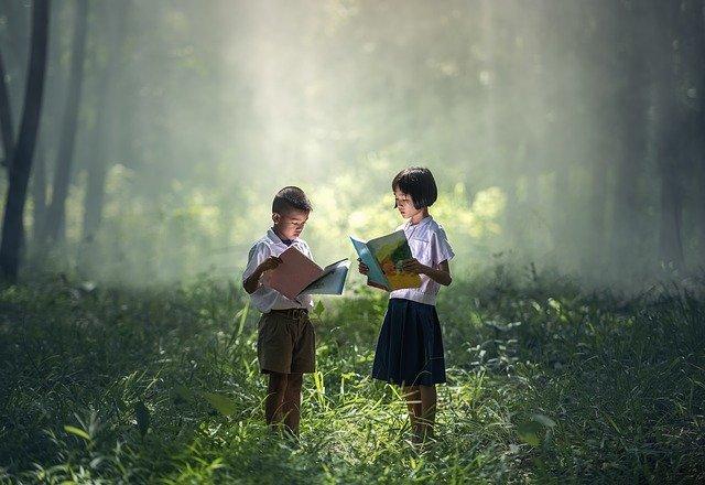 dvě holčičky čtoucí knihu v lese