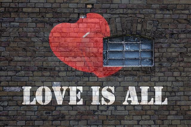 """nápis na cihlové zdi """"láska je vše"""""""